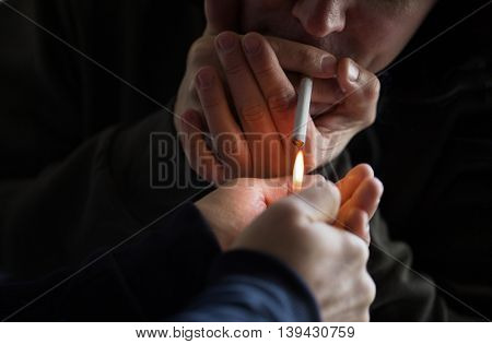 smoking, substance abuse, addiction and bad habits concept - close up of young people lighting cigarette outdoors