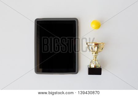 sport, achievement, championship, success and technology concept - close up of golf ball with golden cup and tablet pc computer with black blank screen over white background from top
