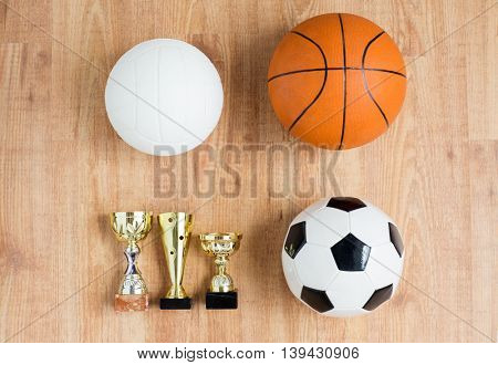 sport, achievement, championship, competition and success concept - close up of different balls and golden cups over wooden background