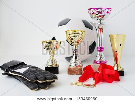 sport, achievement, championship and success concept - close up of football or soccer ball and goalkeeper gloves with golden medals and cups