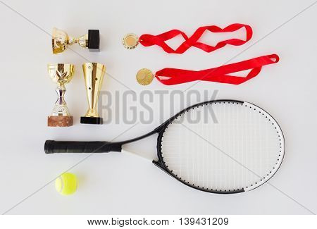 sport, achievement, championship, competition and success concept - close up of tennis racket and ball with cups and medals over white background