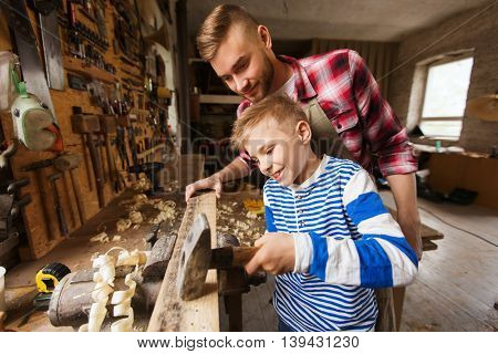 happy family, carpentry, woodwork and people concept - father and little son with hammer hammering nail into wood plank at workshop