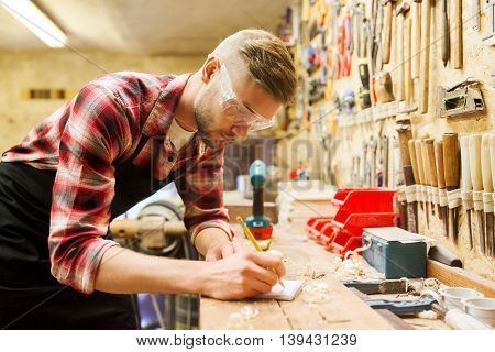 profession, carpentry, woodwork and people concept - carpenter with pencil writing to notebook at workshop
