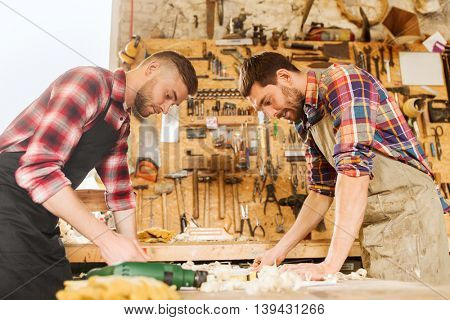 profession, carpentry, woodwork and people concept - two carpenters with blueprint at workshop