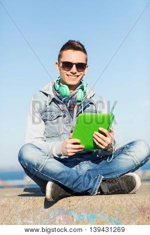 technology, lifestyle, music and people concept - smiling young man or teenage boy with tablet pc computer and headphones outdoors
