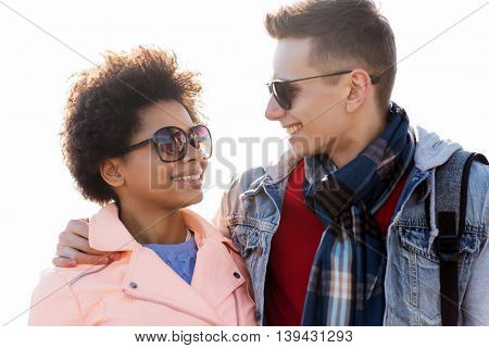 friendship, relations, tourism, travel and people concept - group of happy teenage friends or couple in sunglasses talking outdoors