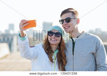 summer, vacation, holidays, technology and friendship concept - smiling couple with smartphone taking selfie outdoors