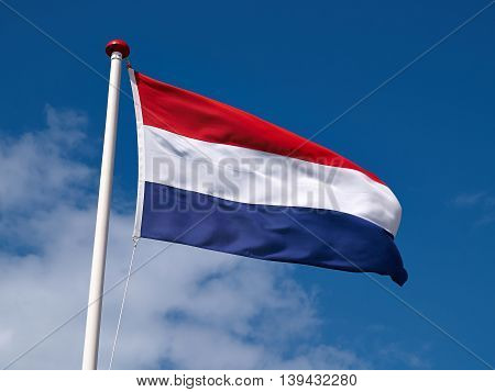 Flag of France high up in the air against blue cloudy sky