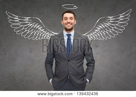 business, angel investor, safety, security and people concept - smiling young businessman with wings and nimbus drawing over gray concrete background