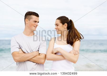 Young couple looking at each other on beach
