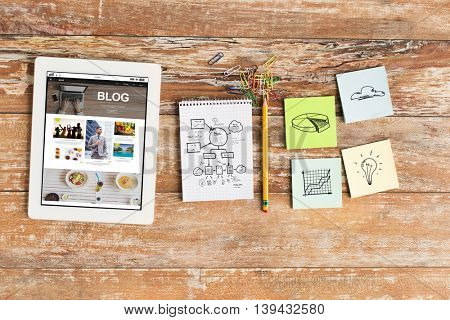 business, education, objects and technology concept - close up of notebook, tablet pc with blog web page on screen and stickers on table