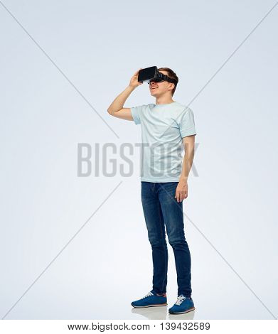 3d technology, virtual reality, entertainment, cyberspace and people concept - happy young man with virtual reality headset or 3d glasses looking at something