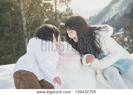 Cute Asian children boy and girl playing with snowman