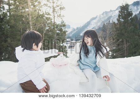Cute Asian children girl and boy playing with snowman