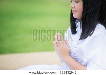 Hand of Asian girl praying in the park