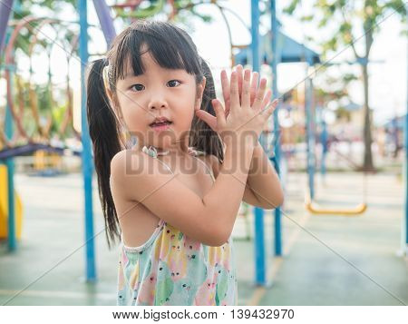 asian baby child playing on playground clap her hands action