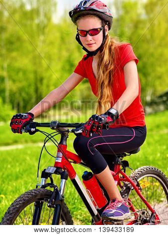 Bicycle child girl. Girl rides bicycle on green grass in park outdoor. Girl in bicycle helmet . Bicycle is good for good mood. Bicycleist is happy.
