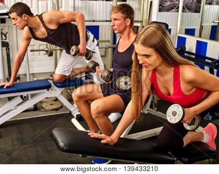 Group of sport people working with dumbbells his body at gym. Men and woman hard work dumbbells in sport gym.