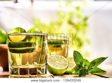 Country cocktail. Wooden boards two glasses with green transparent cocktail and lime glue bowl. Drink two hundred twenty four mojito with mint leaf on sunlight . Country style. Light background.