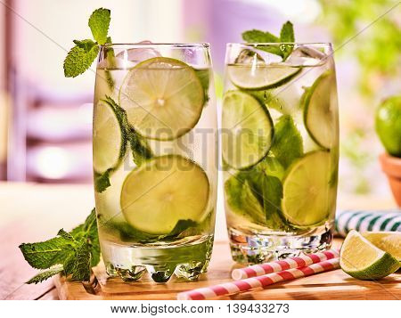 Alcohol cocktail. On wooden boards two glasses with alcohol cocktail and ice cubes. Drink two hundred twenty seven cocktail mohito with straw and lime and mint leaf. Country outdoor. Light background.