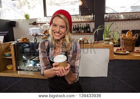 Waitress holding a disposable cup in the cafe