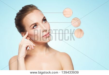 beauty, people, aging and skin care concept - beautiful young woman and circles with magnified facial wrinkles over blue background