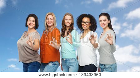 friendship, fashion, body positive, gesture and people concept - group of happy different size women in casual clothes showing ok hand sign over blue sky and clouds background