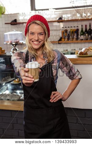 Waitress showing a disposable cup in the cafe