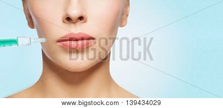 people, cosmetology, plastic surgery and beauty concept - beautiful young woman face and syringe making injection for lips augmentation over blue background