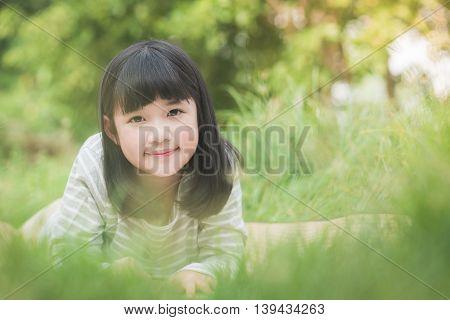Beautiful Asian girl lying on a field