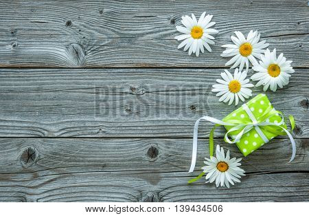 Daisy flowers with a gift box on old wooden board