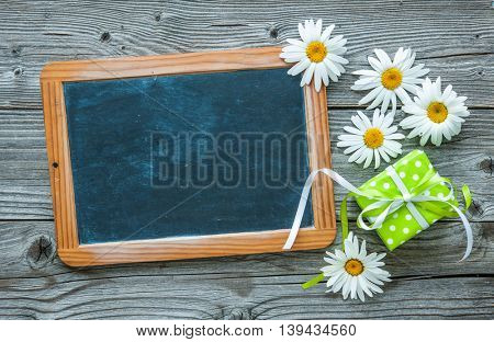 Daisy flowers with blackboard and gift box on old wooden board