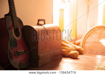Acoustic Guitar On Wooden Table With Chest