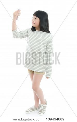 Beautiful Asian girl making selfie photo on smartphone isolated on a white background