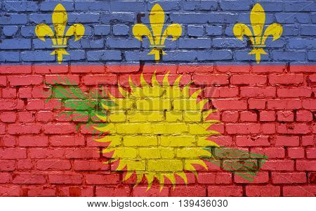 An image of the Guadeloupe flag painted on a brick wall in an urban location