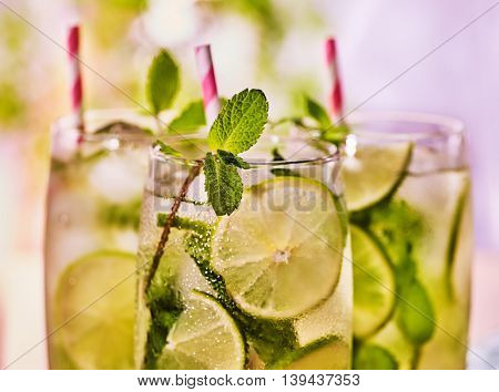 Alcohol fruit cocktail. On wooden boards top of three glasses with alcohol cocktail drink and ice cubes. Drink two hundred twenty eight cocktail mohito and cube ice with straw. Light background.