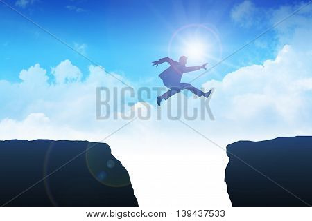Silhouette of man jumping over the ravine