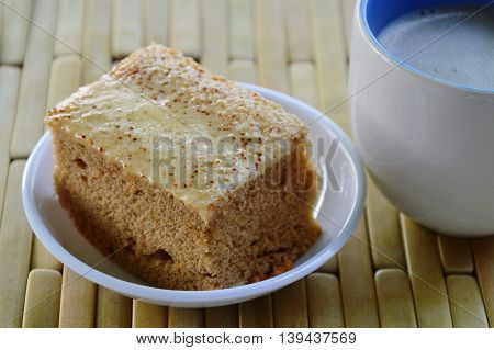 cake and milk coffee on bamboo plate