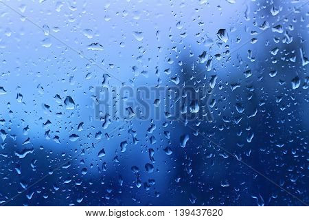 Natural blue background with water drop on glass