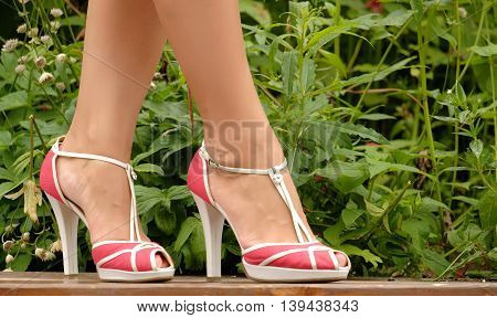Beautiful female feet in sandals close-up outdoors