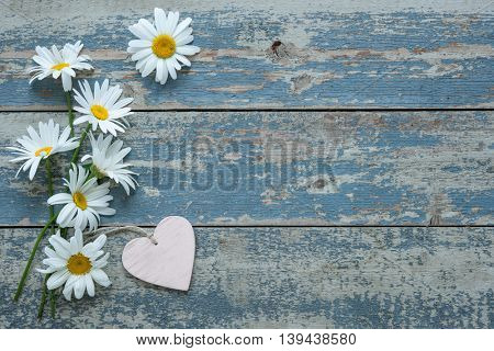 Daisy flowers with a heart shaped tag on old wooden background