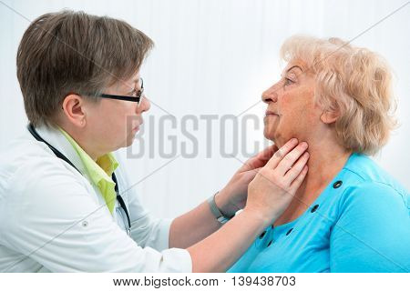 Thyroid function examination. Doctor touching the throat of a patient in the office