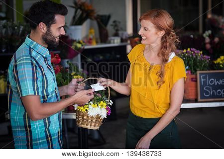 Female florist giving visiting card and flower basket to customer in the flower shop