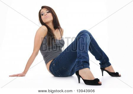 Beautiful girl in jeans sitting on the floor