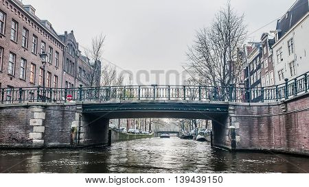 Amsterdam Holland, 4 December 2014 : Canal Cruises view of Amsterdam. Amsterdam is the Netherlands' capital, known for its artistic heritage, elaborate canal system and narrow houses with gabled facades, legacies of the city's 17th-century Golden Age.
