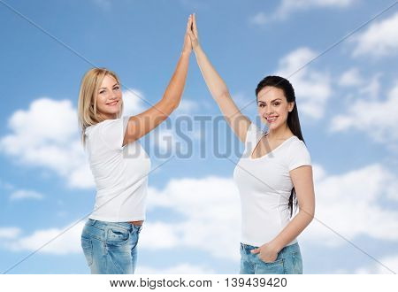 friendship, diverse, body positive, gesture and people concept - group of happy different women in white t-shirts making high five over blue sky and clouds background