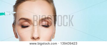 people, cosmetology, plastic surgery, anti-aging and beauty concept - beautiful young woman face and syringe making lifting injection to forehead over blue background