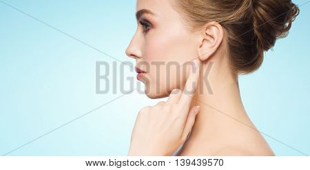 health, people and beauty concept - beautiful young woman pointing finger to her ear over blue background