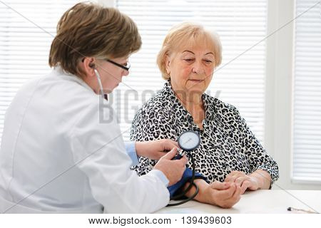 Doctor checking elderly womans blood pressure