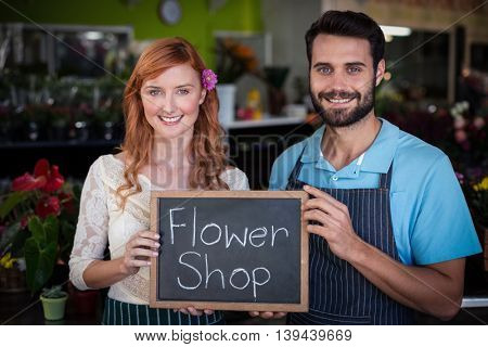 Portrait of couple holding slate with flower shop sign in the flower shop